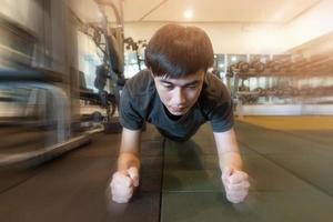 hombre de fitness está planchando en el gimnasio foto