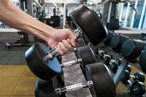 mano humana, tenencia, pesa de gimnasia, en, gimnasio foto