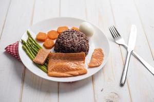 Health food concept, salmon with rice and vegetable on wood background photo