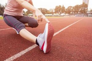 Close up sporty woman is Stretch in sport field photo