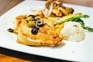 Grilled sea bass fish meat steak in white plate photo