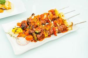 Grilled bbq meat stick in white plate photo