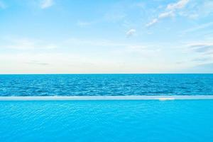 Infinity swimming pool with sea and ocean view on blue sky photo
