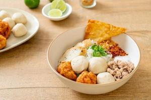 Fideos de arroz planos pequeños picantes con bolas de pescado y bolas de camarones sin sopa - estilo de comida asiática foto