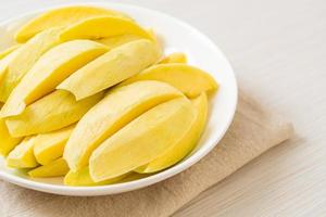 Fresh green and golden mango sliced on plate photo