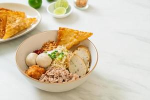 Fideos de huevo picantes con bolas de pescado y bolas de camarones sin sopa - estilo de comida asiática foto