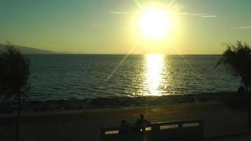 Leute, die bei Sonnenuntergang auf einer Bank in Ufernähe sitzen video