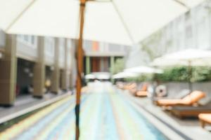 Abstract blur and defocused umbrella and chair around swimming pool photo