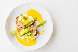 Eggs benedict with bacon twist asparagus photo