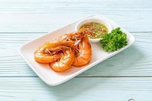 Baked salted shrimps or prawns with seafood spicy sauce - seafood style photo
