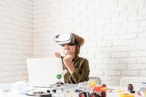 Sonriente jovencito en gafas de realidad virtual jugando, el enfoque selectivo foto