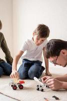 Father and boys having fun constructing robot cars at home sitting on the rug photo