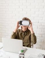 muchacho adolescente en gafas de realidad virtual jugando el juego foto