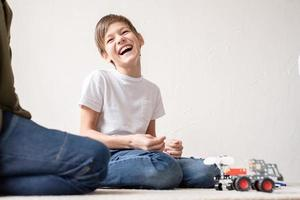 Young boys having fun constructing robot cars at the workshop photo