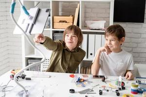 Los muchachos se divierten haciendo coches robot viendo el programa educativo en tableta digital foto