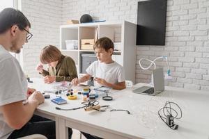 Los niños y el profesor se divierten construyendo coches robot en el taller. foto