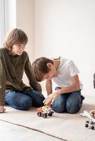 Young boys having fun constructing robot cars sitting on the rug photo