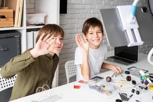 Los muchachos se divierten haciendo coches robot con clase en línea en tableta digital foto