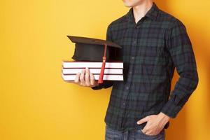 El hombre universitario está contento con la graduación sobre fondo amarillo foto