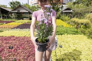 linda chica está sosteniendo una maceta de flores foto