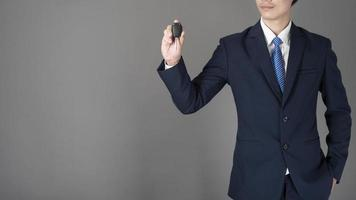 Business man is holding car key, grey background in studio photo