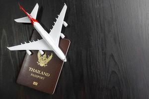 Airplane model and passport on wooden desk, ready travel concept photo