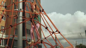 uma criança sobe em uma barra horizontal de corda em um parquinho ao ar livre video