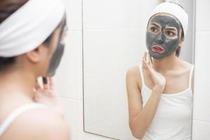 Bella mujer enmascarando su rostro sobre fondo blanco. foto