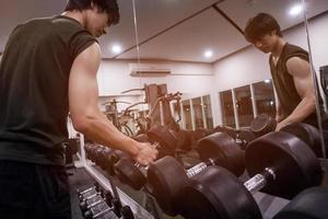 Cerca del hombre sujetando el peso en el gimnasio foto