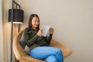 Portrait beautiful young asian women reading book and sitting on sofa chair photo