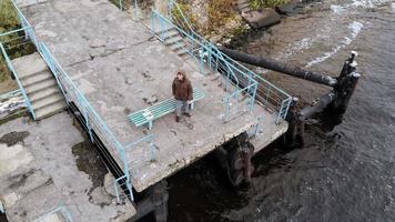 um homem controla um drone voando sobre ele e o rio video