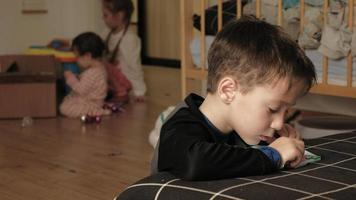 A preschooler boy plays with peeler beads with other children in the background video
