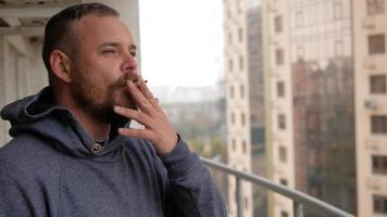 un hombre con barba está parado en el balcón video