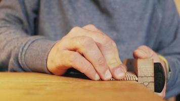 Joiner's hands planing a wooden comb with a plane video