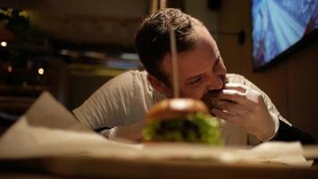 Mann mit Bart isst einen Cheeseburger video