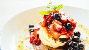 Panqueques con frutos rojos mixtos en la placa blanca. foto