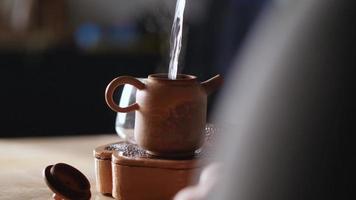 een man giet kokend water in een theepot van klei video