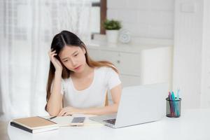 Dolor de cabeza de joven mujer asiática durante el trabajo en la computadora portátil con fecha límite en el escritorio en casa, mujer de negocios con fracaso agotada y cansada, estresada y preocupada, frustrada y sin éxito. foto