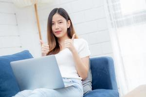 Young asian business woman smile and work from home with laptop computer online to internet on sofa in living room, freelance girl using notebook on couch with comfort, new normal, lifestyle concept. photo
