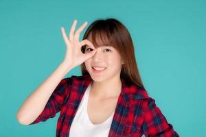 hermosa mujer asiática joven feliz usar viajes verano gesto ok signo con la mano en el ojo con visión aislada sobre fondo azul, expresión de niña adolescente de asia con alegre y divertido durante el viaje. foto