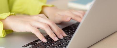 Primer plano de la mano joven empresaria asiática trabajando en la computadora portátil en el escritorio en la oficina en casa, freelance mirando y escribiendo en el cuaderno en la mesa, mujer estudiando en línea, concepto de negocios y educación. foto