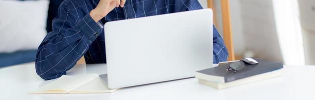 Hombre de negocios asiático joven que planea trabajar y usar la computadora portátil en el escritorio en casa, notas sobre finanzas, estudio y aprendizaje masculino, idea de pensamiento de hombre de negocios, concepto de negocios y comunicación. foto
