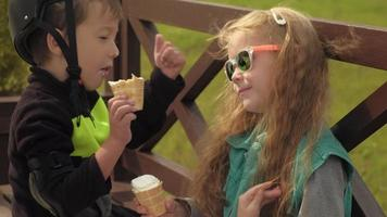 A boy and a girl are sitting on a park bench and eating ice cream Summer video