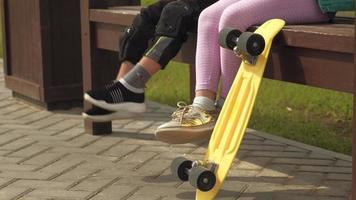 Children are sitting on a bench moving their legs a yellow skateboard is standing next to it video