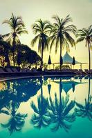Silueta de palmera de coco alrededor de la piscina foto