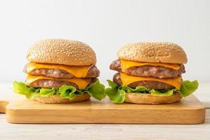 Hamburguesa de cerdo o hamburguesa de cerdo con queso sobre tabla de madera foto