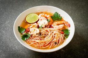 Noodles with spicy soup and shrimps in white bowl, or Tom Yum Kung - Asian food style photo