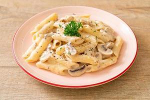 Penne pasta carbonara cream sauce with mushroom - Italian food style photo