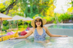 Beautiful young asian women happy smile relax around outdoor swimming pool in hotel resort for travel in holiday vacation photo