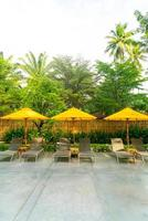 Umbrella and pool bed decoration around swimming pool in hotel resort photo